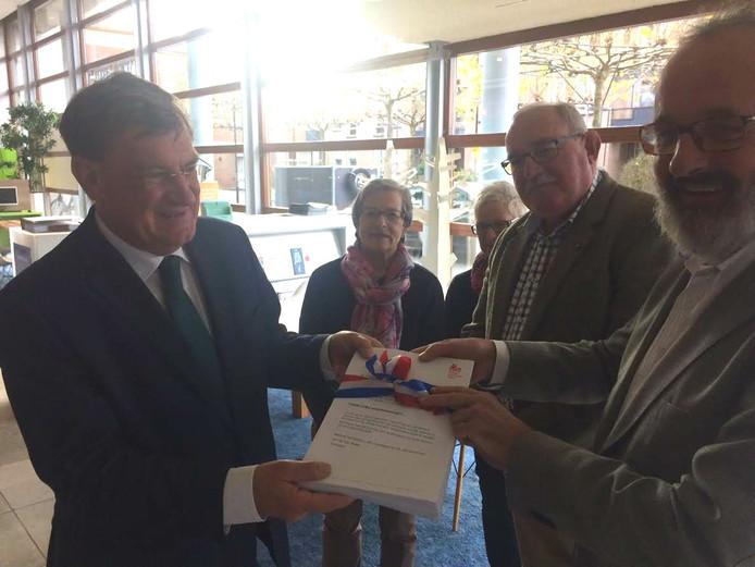 Burgemeester Henk Hellegers ontvangt het pak handtekeningen van voorzitter Luc van den Brule. Op de achtergrond bestuurslid Thom Beuker.