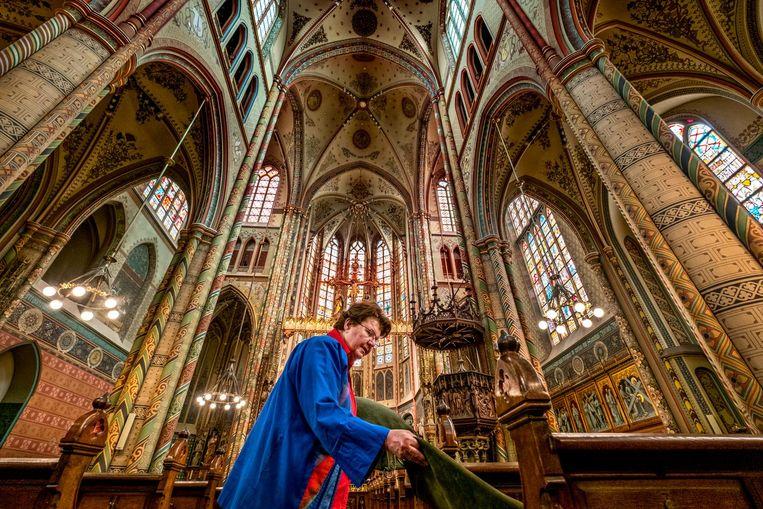 Aggie van den Eijnden legt de kussens neer in de kerkbanken van de Sint Willibrordkerk. Beeld null