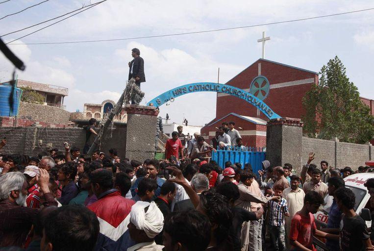 Gelovigen en reddingswerkers bij een van de kerken na de aanslag. Beeld reuters