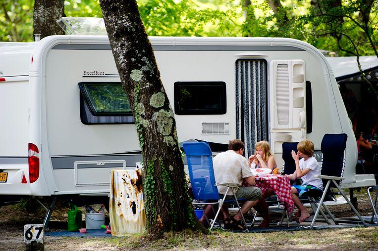 Vakantiegangers eten naast hun caravan op camping Domaine Le Pommier in het Franse Villeneuve-de-Berg (Ardeche). Beeld ANP