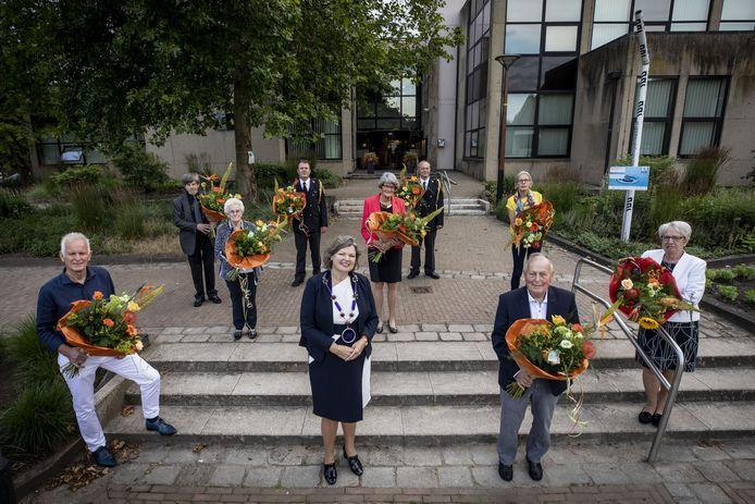 Negen inwoners van Tubbergen krijgen alsnog koninklijke onderscheiding. Foto met gedecoreerden op anderhalve meter van elkaar, met burgemeester Wilmien Haverkamp.