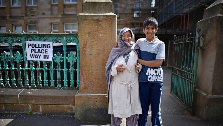 Een kiezer met haar zoon in Glasgow. Beeld ap