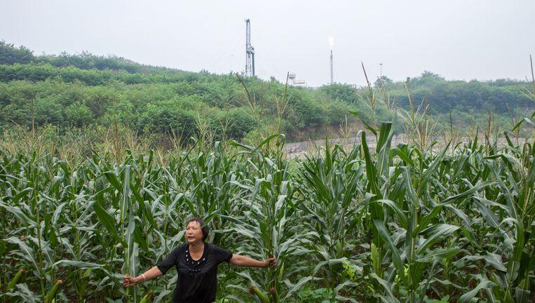 Mevrouw Zheng in het maisveld van het dorp Xinhua met op de achtergrond een vlam en boortoren van schaliegas winning Beeld WassinkLundgren