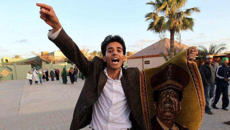 Een aanhanger van Kadhafi, met een portret van de Libische leider, in Tripoli. Beeld epa