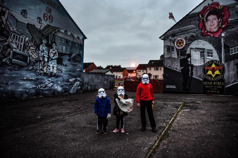 Kinderen in Belfast. In de achtergrond een geschilderd eerbetoon aan paramilitaire unionisten. Beeld Laetitia Vancon/The New York Times