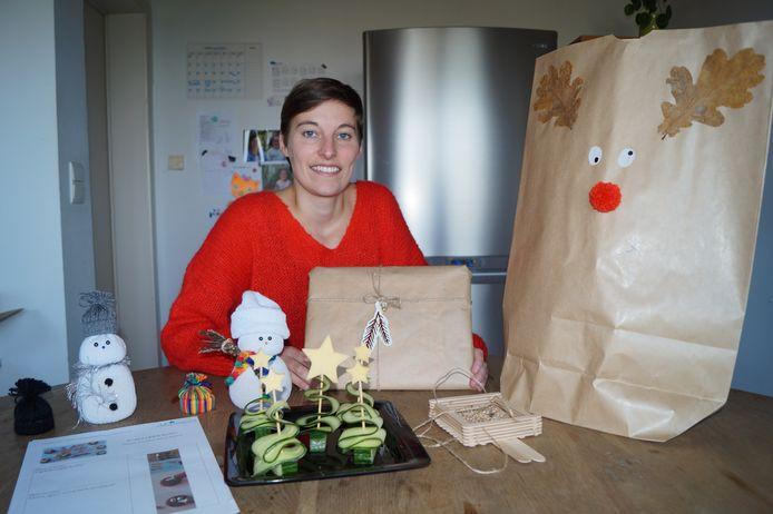 Lien De Zutter met (een selectie van) de inhoud van de Glunderpakketten. We zien onder meer een sneeuwman en een voederplankje voor vogels, maar ook enkele hapjes uit het kookpakket, helemaal in kerstthema.