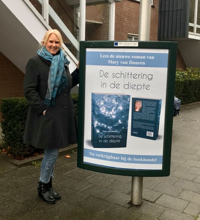 Mary van Duuren bij een billboard met reclame voor haar debuutroman.