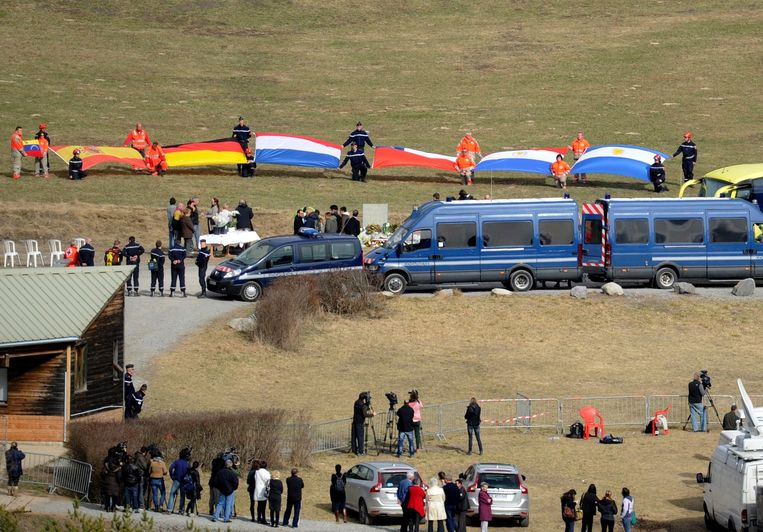 Politieagenten houden vlaggen omhoog tijdens een ceremonie voor de familieleden van de slachtoffers van de vliegramp. Beeld afp