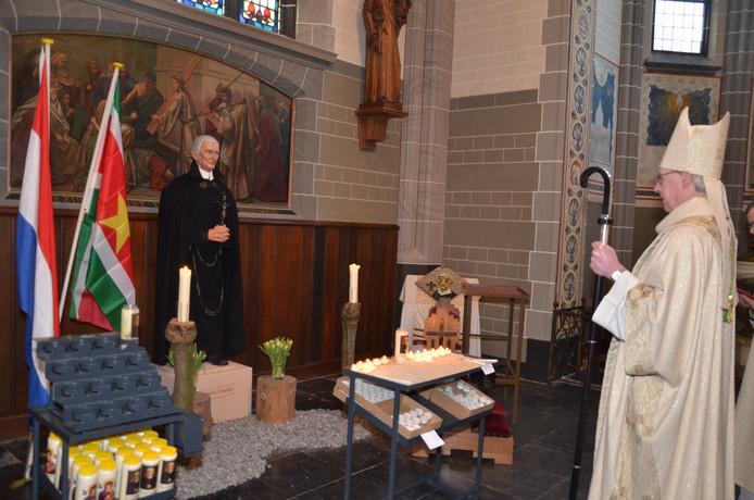 Bisschop Gerard de Korte neemt tijdens de mis even de tijd voor bezinning bij het beeld van Peerke Donders.