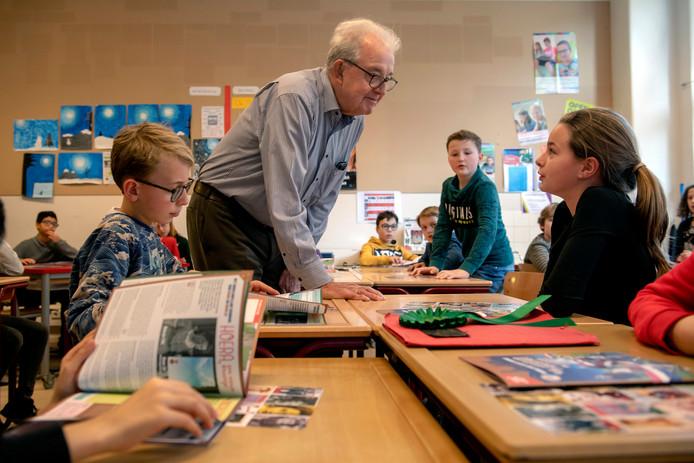 Aart Markus beantwoordt vragen over de oorlog in groep 7/8 van basisschool De Elzen in Tilburg, terwijl leerlingen bladeren in de stickerboekjes.