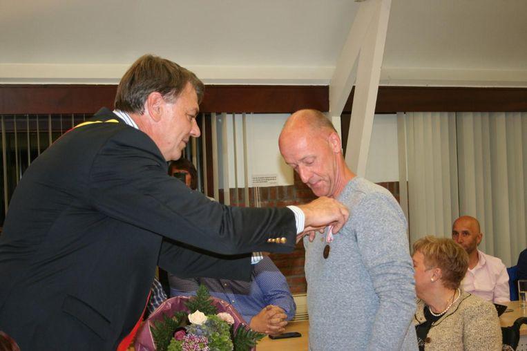 Burgemeester Claes spelt de medaille op bij Dirk.