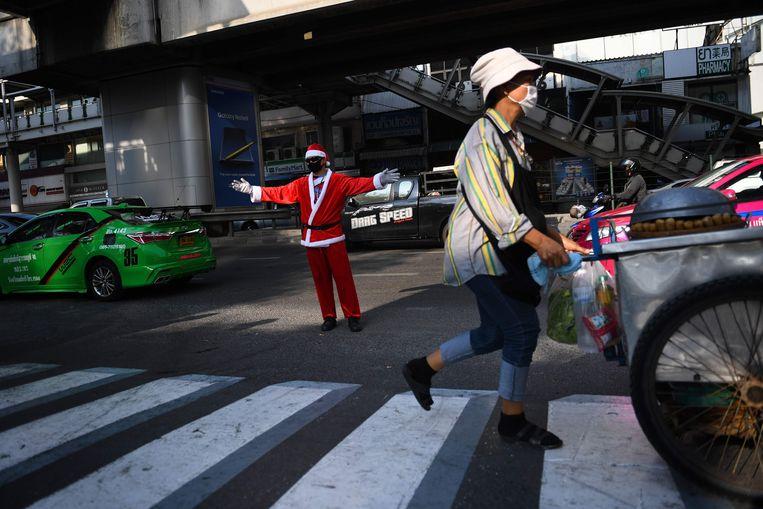Een 'kerstman' regelt het verkeer in Bangkok.