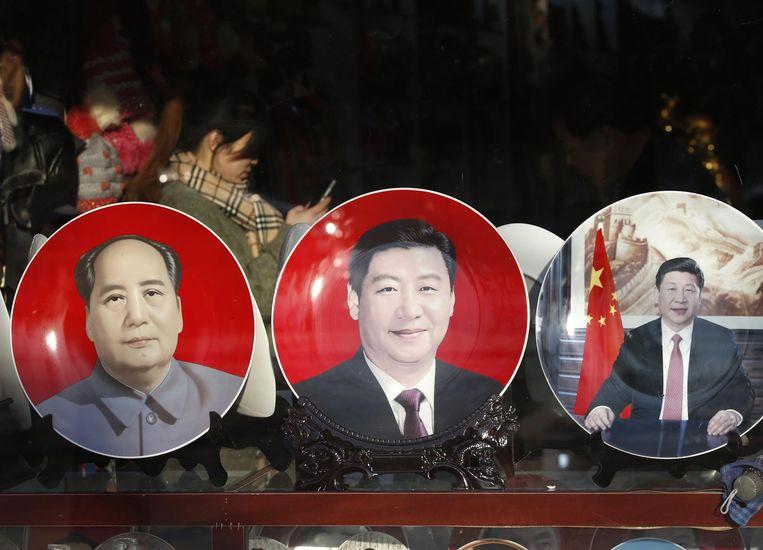 Bordjes die Xi Jinping en Mao Zedong afbeelden worden als souvernirs verkocht Beeld reuters