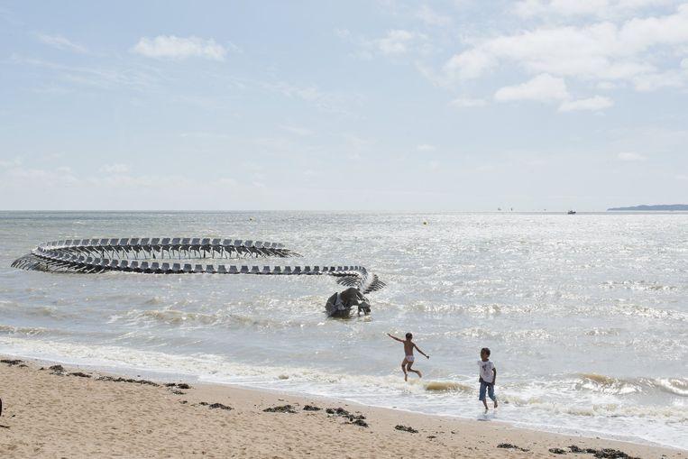 De metalen zeeslang van kunstenaar Huang Yong Ping kronkelt de oceaan uit bij de badplaats Saint-Brévin-les-Pins. Beeld Martin Argyoglo