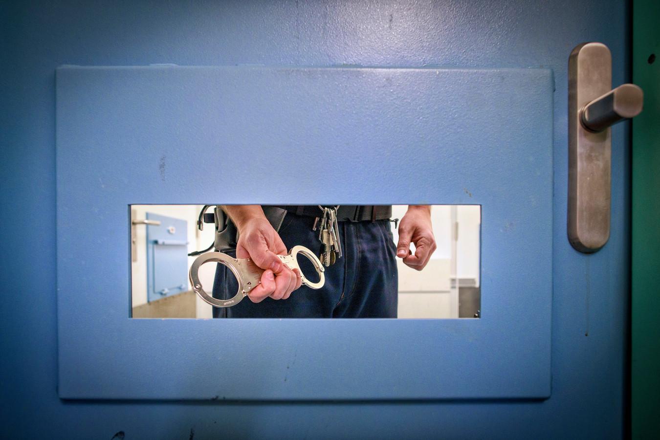 Een bewaarder met handboeien achter de celdeur. Foto Dolph Cantrijn