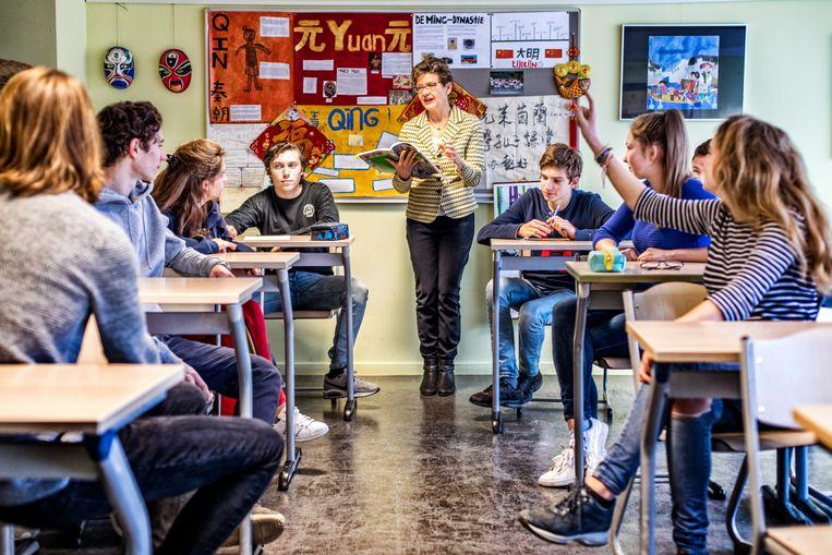 Leerlingen van een lyceum in Wassenaar bespreken het net gemaakte examen Chinees met docent Gwendolyn Tates.  Beeld null