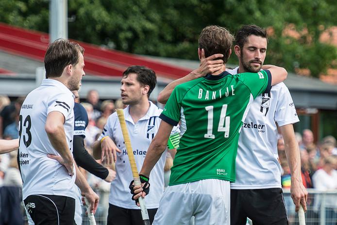 De spelers van Zwart-Wit en Push (groen) troosten elkaar nadat beide ploegen uit de promotieklasse degraderen.