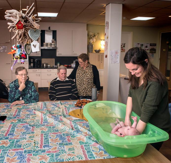 Linda Sandberg doet haar dochter Juliët in bad terwijl activiteitenbegeleidster Patricia Sandberg met enkele bewoners toekijkt.