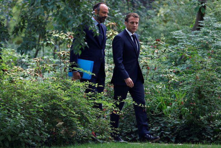 De Franse president Macron en ex-premier Edouard Philippe. De twee zijn in veel opzichten elkaars tegenpolen.  Beeld EPA