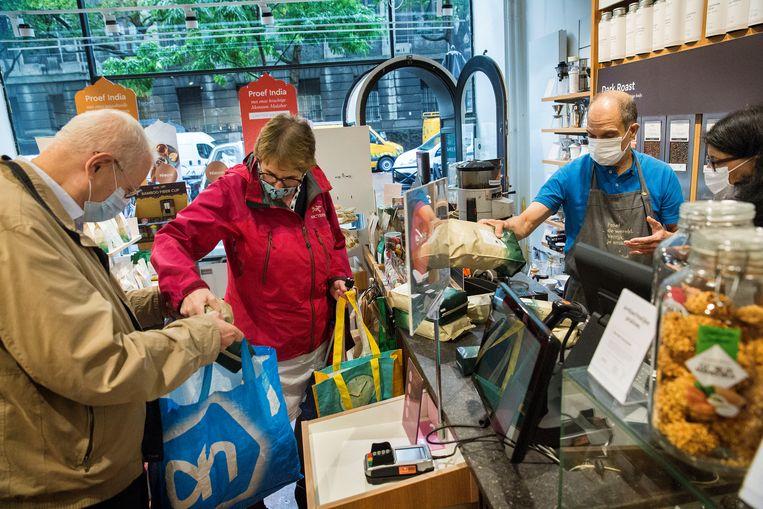 Bezoekers van een winkel in Rotterdam dragen een mondkapje. Beeld Arie Kievit