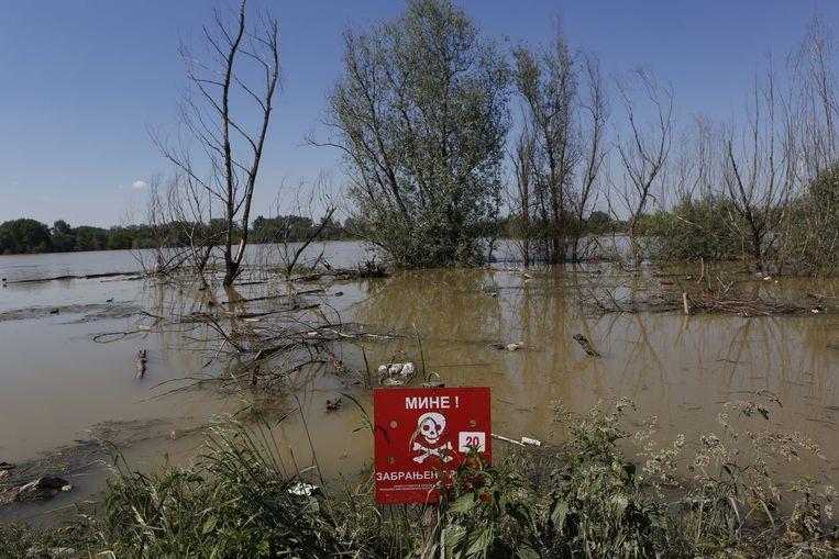 Een bord met 'mijnenveld' erop, op de oever van de rivier Sava. Beeld ap