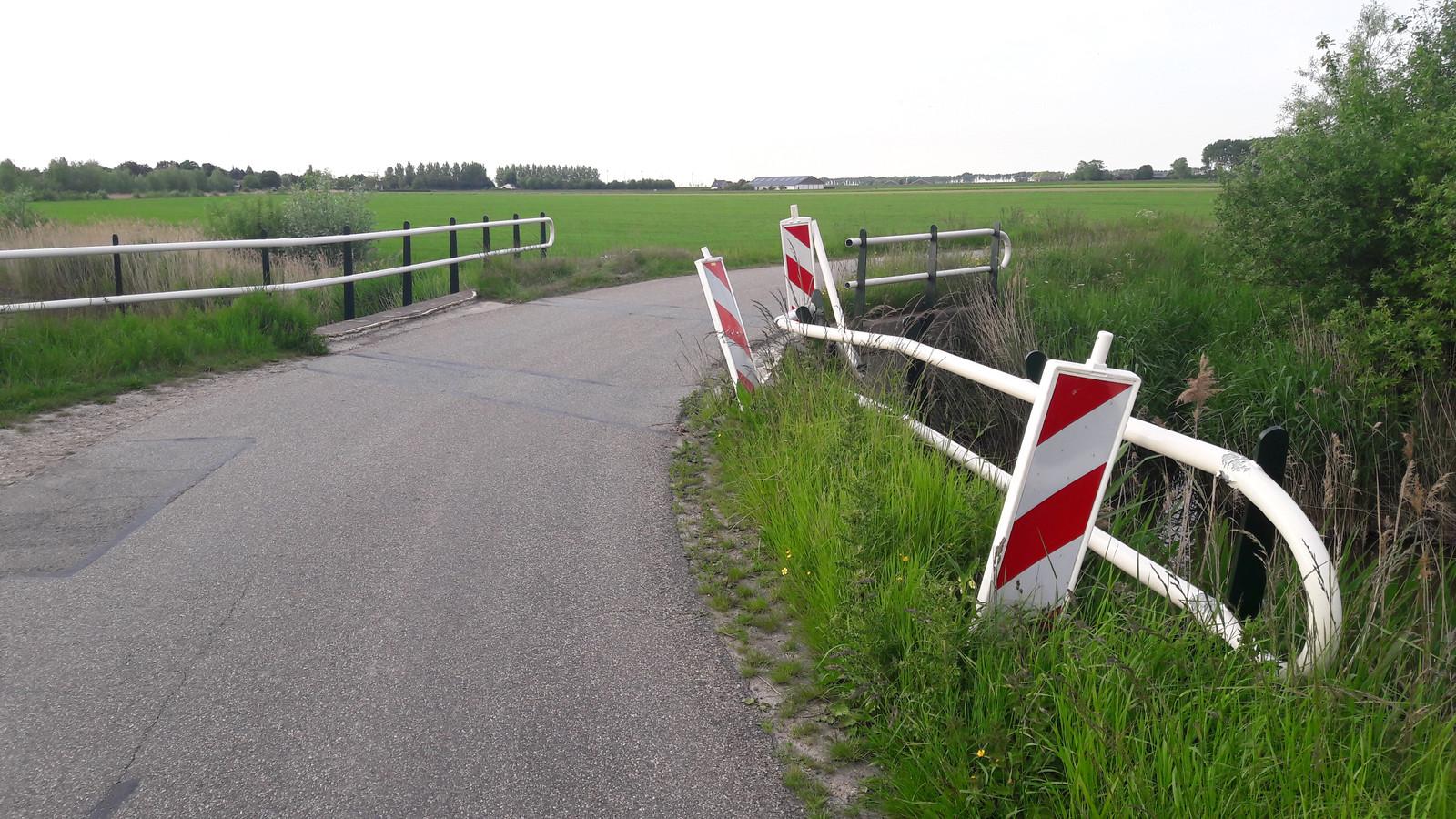 Een bocht in de Lange Betteweg bij Biervliet, de reling van de brug over de watergang is inmiddels kapot gereden.