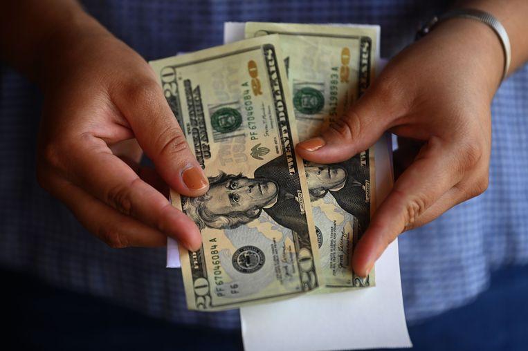 Een vrouw telt geld buiten een geldkantoor in San Isidro, in San Salvador, dat overboekingen uit de VS afhandelt. Beeld AFP