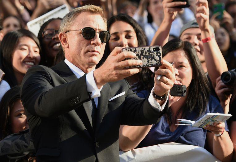 Acteur Daniel Craig neemt een selfie op de rode loper. Beeld AP