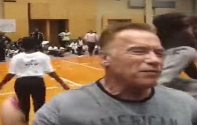 Arnold Schwarzenegger juste avant d'être frappé au dos par un individu.