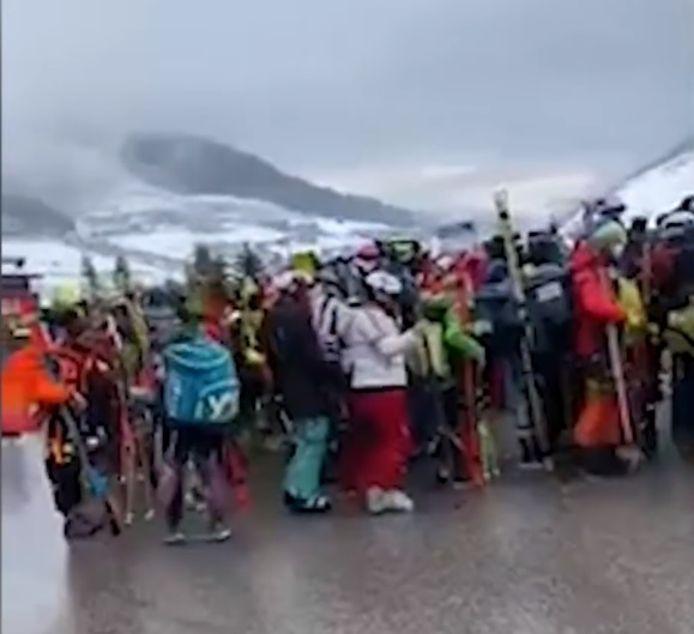 Een lange rij met wintersportfanaten aan de kabelbaan.