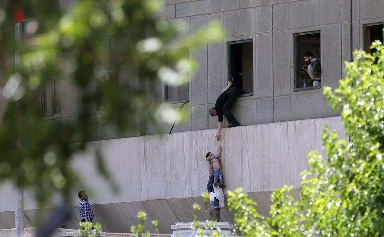 Agenten brengen mensen in veiligheid bij het parlementsgebouw in Teheran, tijdens de aanval van de terroristen. Beeld EPA