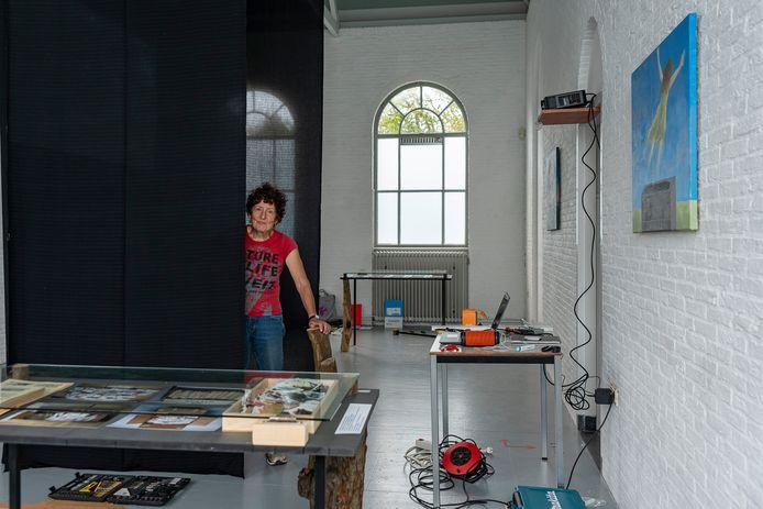 Digna Sinke is bezig met de opbouw van haar expositie in de Bewaerschole. Tussen de zwarte doeken is haar film te zien