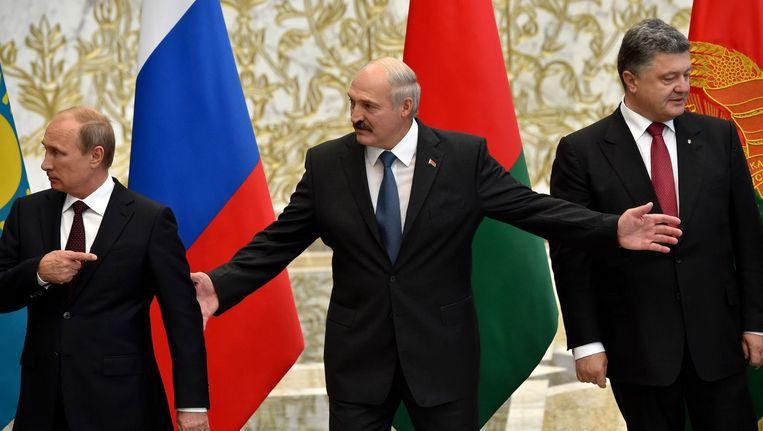 Vladimir Poetin (l) en Petro Porosjenko poseren met president Aleksander Loekasjenko (midden) tijdens het overleg in Wit-Rusland. Beeld anp