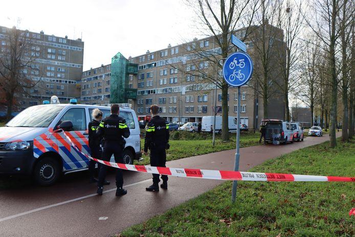Het gebied rond de flat is afgezet. Agenten in kogelvrije vesten houden het pand in de gaten.