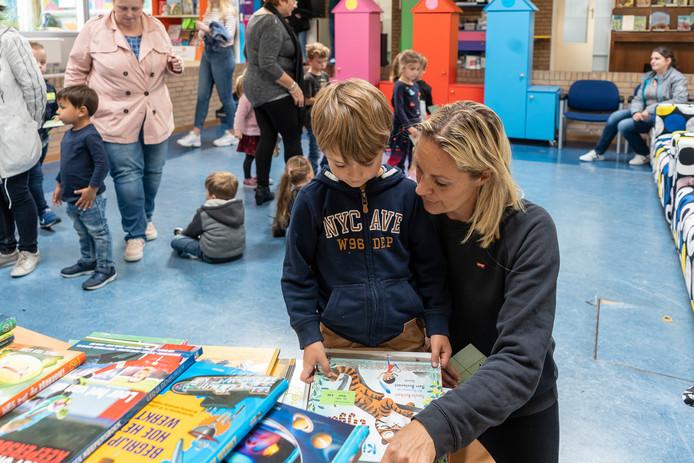 Jens Franke kiest samen met zijn moeder zijn nieuwe boek uit dat hij mag kopen met de cadeaubon.