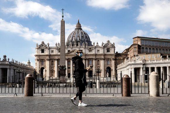 Een voorbijganger met mondmasker ging zondag langs het verlaten Sint-Pietersplein in Vaticaanstad (Rome).  De paus geeft zijn wekelijkse preek nu via internet.