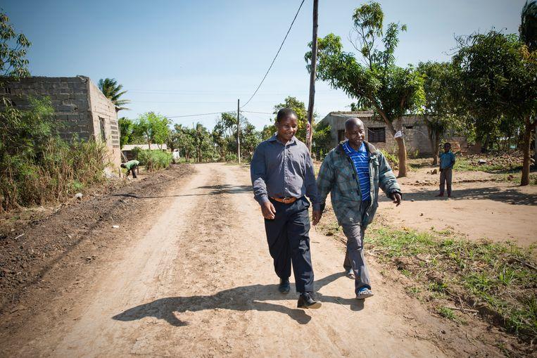 Raposo Rego (links) en de secretaris van Rego's kerk Luis Companhia wandelen door de dorpsstraten naar Rego's kerk.  Beeld Bram Lammers