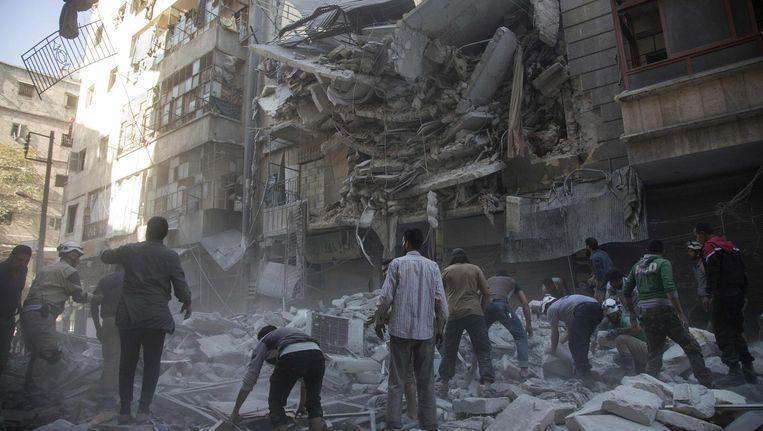 Syrische burgers bij door bombardementen verwoeste gebouwen in Al-Shaar, Aleppo Beeld afp