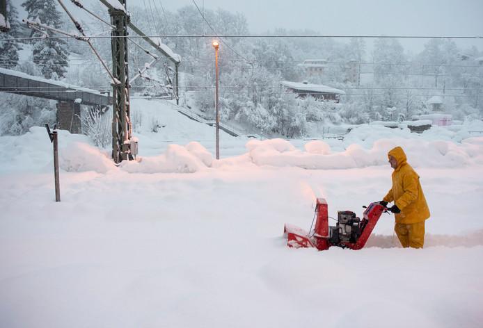 Een man gebruikt een sneeuwblazer om een wandelpad te maken bij een treinstation in het Duitse Berchtesgaden.
