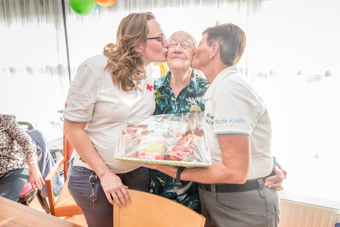 Nel Bijl-Vermaas is met haar 100 jaar de oudste actieve vrijwilliger van het Rode Kruis. Zij wordt door Josina Bevelander (links) en Ester Geldenhuys (rechts) van het Rode Kruis gefeliciteerd.