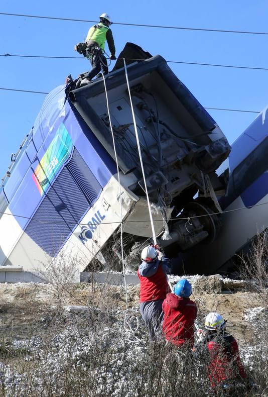 Reddingswerkers aan het werk bij de ontspoorde trein.