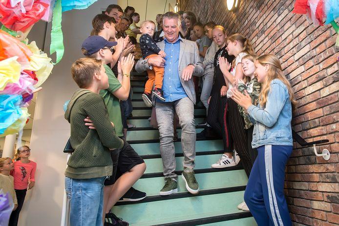 Directeur Jan Smits neemt onder applaus van de leerlingen afscheid van De Vonder. Op zijn arm zijn kleinzoon.