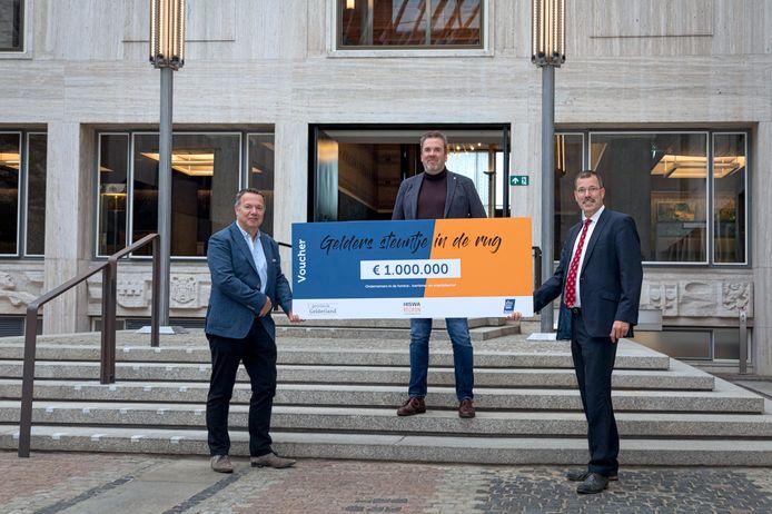 Gedeputeerde Peter van 't Hoog (rechts) en Sander Wind van KHN Gelderland (midden) overhandigen symbolisch één miljoen euro aan de Gelderse ondernemer Edwin Bomers (links).