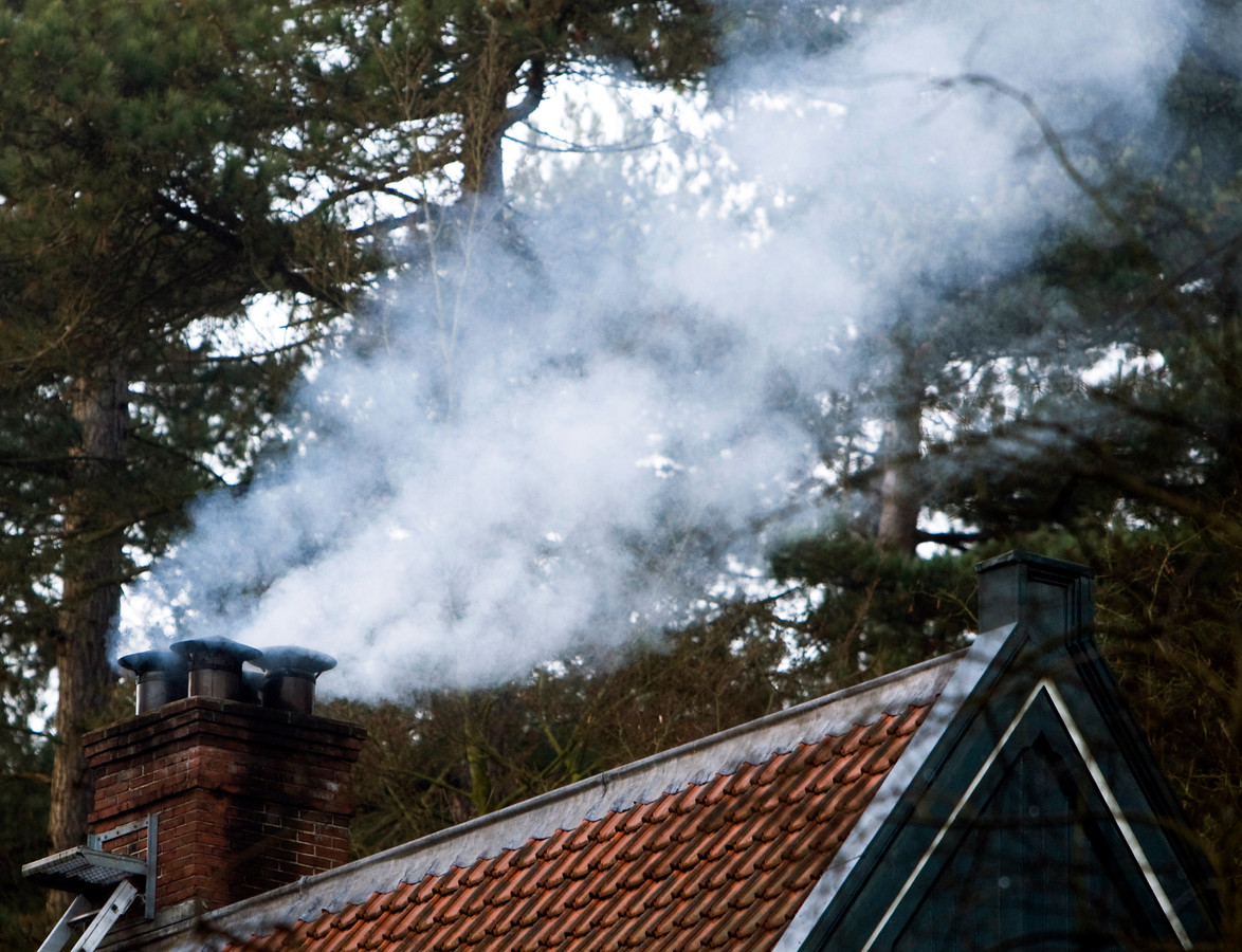 Rook uit de schoorsteen van een huisje in het bos.