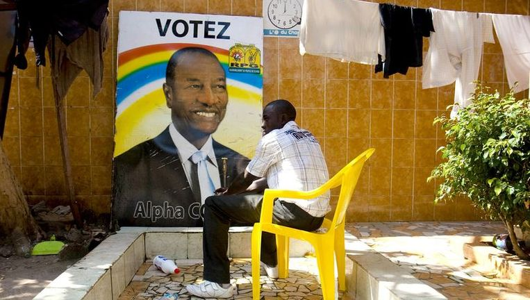 Een man in Guinee voor een verkiezingsposter van Condé. Beeld reuters