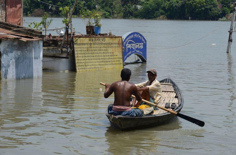 Indiase inwoners varen door overstroomd gebied.  Beeld AFP