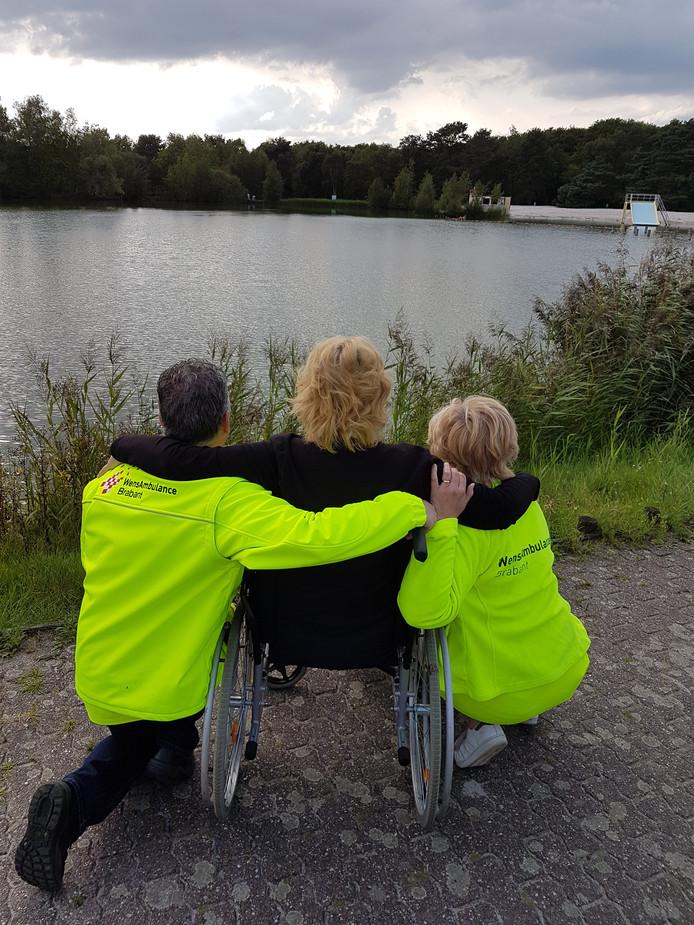 Dion Schepens (links) en een collega van Wensambulance Brabant slaan de handen om de schouders van een terminale patiënte.