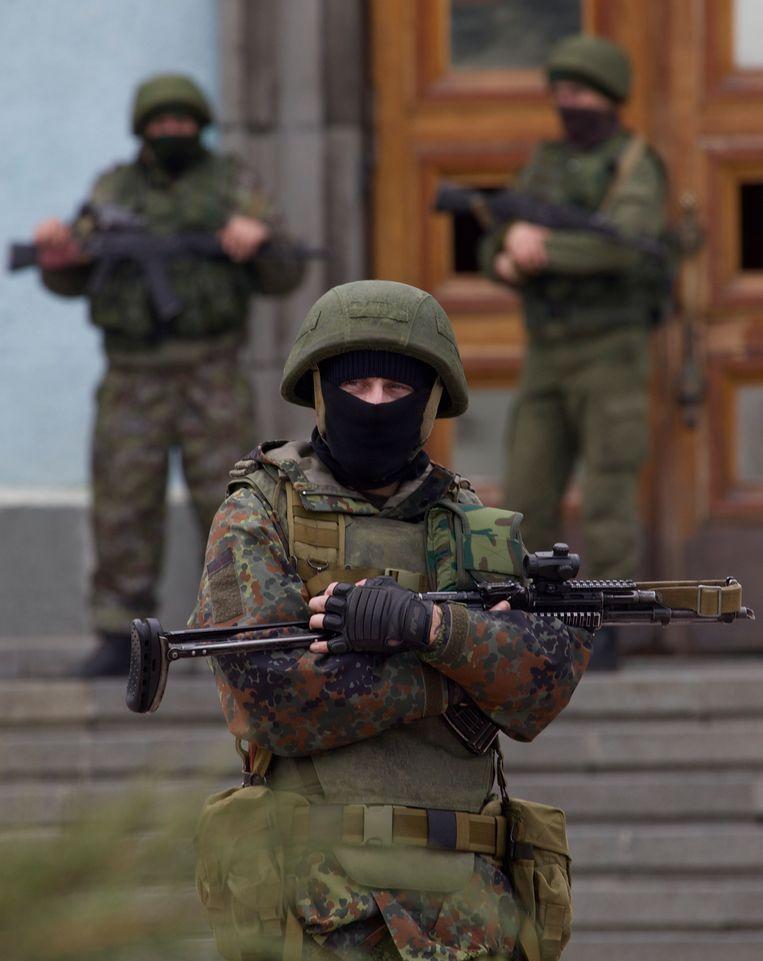 Militairen zonder insigne bewaken het parlementsgebouw van de Krim in Simferopol. Achteraf bleken de 'groene mannetjes' speciale eenheden van de Russische strijdkrachten te zijn die de taak hadden de annexatie van het Oekraïense schiereiland voor te bereiden. Beeld AP