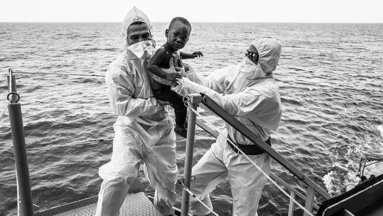 Hulpverleners van een Italiaans marineschip op de Middellandse Zee brengen een Afrikaans kind uit een boot met vluchtelingen in veiligheid Beeld photo_news