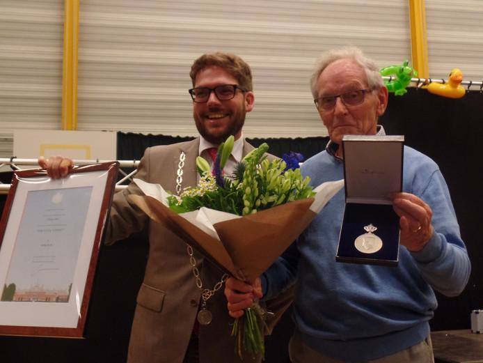 Erelid Johan Saaltink (82), tevens een van de oprichters van de Vereniging Contact Barchem, neemt de Koninklijke Erepenning en de bijbehorende oorkonde in ontvangst uit handen van Sebastiaan van 't Erve, burgemeester van de gemeente Lochem.